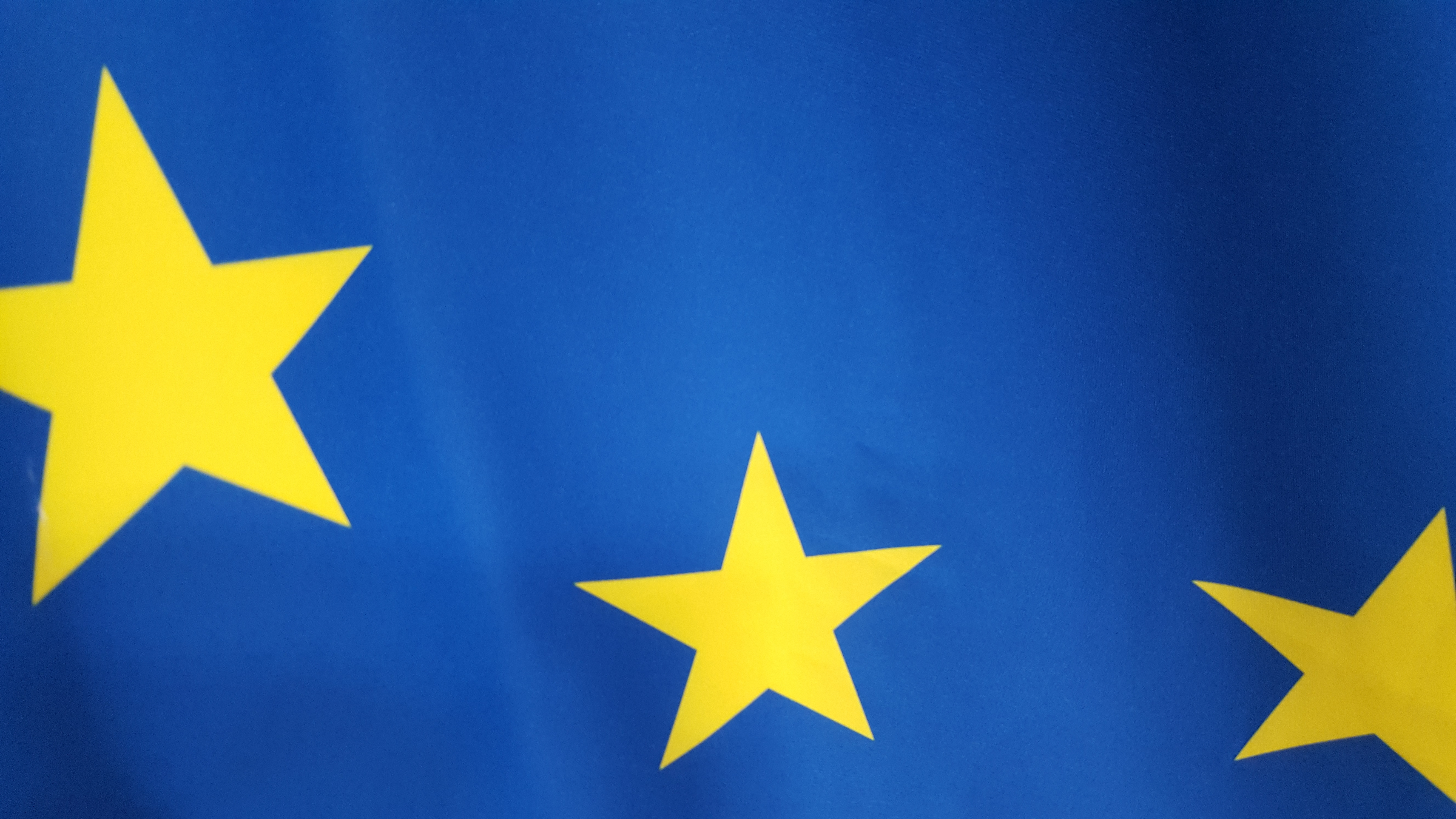 Izsek zastave Evropske unije. Modra podlaga na kateri so tri rumene peterokrake zvezde.