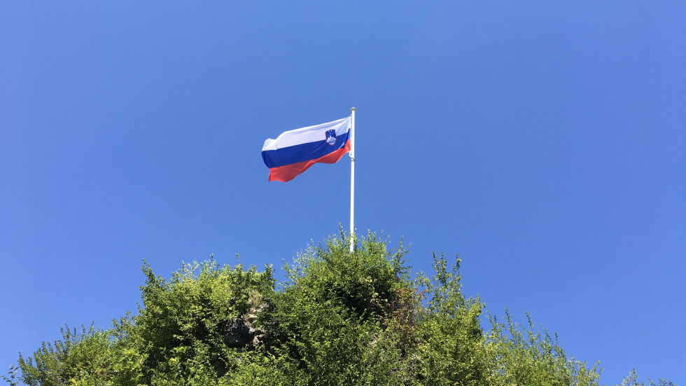 Zastava visi na drogu na hribu in plapola na modrem nebu, pod drogom pa se vidi zeleno drevje