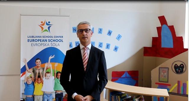 Minister stoji v učilnici in govori v kamero. V ozadju je plakat Evropske šole ter kotiček s knjigami.