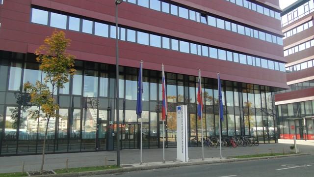 Fotografija stavbe Ministrstva za izobraževanje, znanost in šport s ceste. V ospredju je steber z napisom naziva ministrstva in zastave, v ozadju stavba