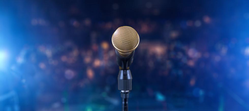 Pogled s koncertnega odra: mikrofon v ospredju, v ozadju pa zamegljena publika
