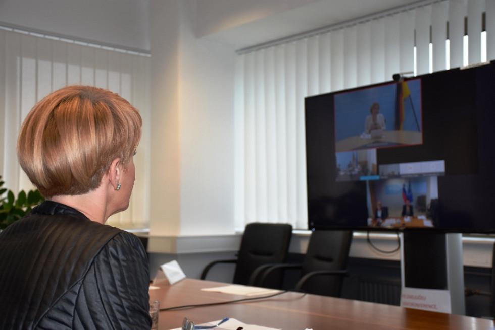Ženska za pisalno mizo med video konferenco