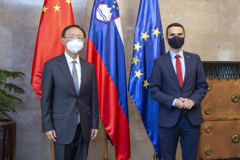 Minister in visoki kitajski gost pred zastavami Kitajske, Slovenije in EU