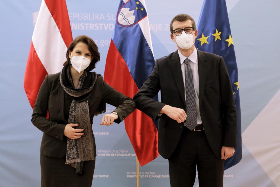 Državni sekretar Dovžan in ministrica Edtstadlerjeva pred zastavami