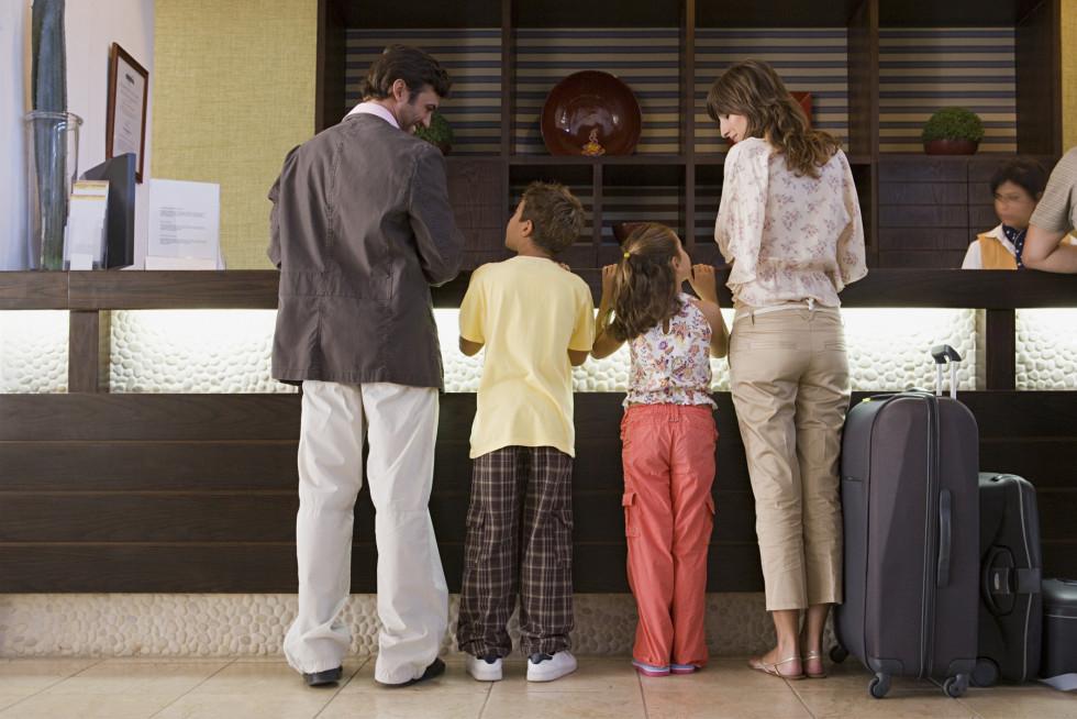 Štiričlanska družina stoji na recepciji hotela