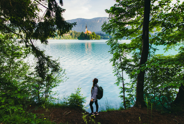 Woman traveler exploring the scenic mountain lake Bled in Julian Alps.