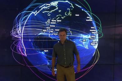 Marko Grobelnik stoji, za njim je digitalni prikaz sveta.