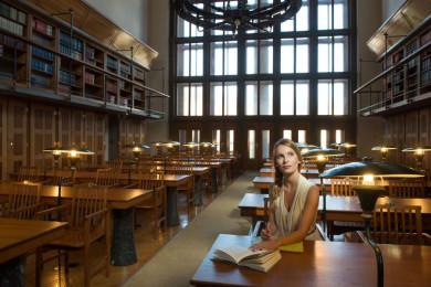 Dekle sedi za mizo v Narodni univerzitetni knjižnici. Na mizi ima knjigo in zvezek za zapiske. Dekle zre navzgor.