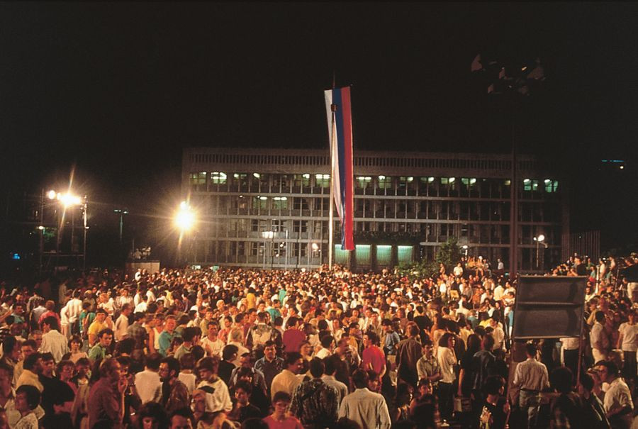 A crowd in Republic Square. There's a parliament in the background and a raised flag.