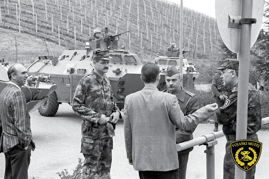 Ljudje, med njimi vojak, se pogovarjajo na cesti. V ozadju tank.