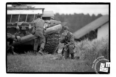 Trije vojaki jugoslovanske armade ob tanku. Eden čepi s puško v roki in kadi cigareto, druga dva sta pri tanku.