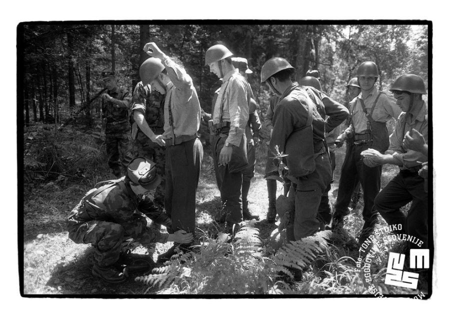 Vojak Teritorialne obrambe pregleduje vojaka jugoslovanske armade (JA), ki drži roke navzgor. Ostali vojaki JA stojijo v vrsti.