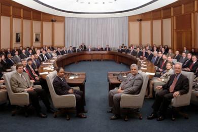 Guvernerji sedijo v polkrogu v dvorani.