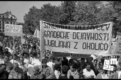 Množica ljudi, v rokah držijo napise. Na enem piše: Sindikat delavcev gradbene dejavnosti Ljubljana z okolico.
