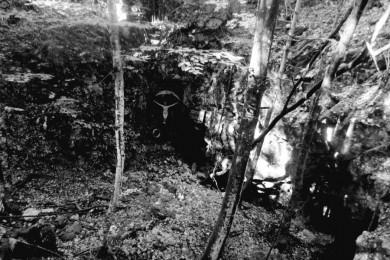Gozd, jama, postavljen je križ.