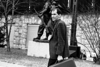 Janez Janša s kovčkom v roki hodi po cesti.