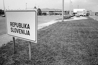 Tabla Republika Slovenija, prazna cesta, carina, parkirani avtomobili na desni strani.