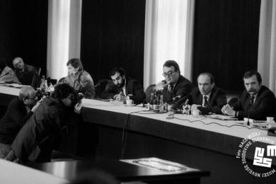 Janez Drnovšek sedi za mizo in govori na tiskovni konferenci. Poleg sedijo ostali govorci.