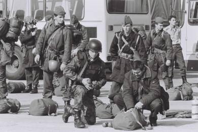 Vojaki JA stojijo, v ospredju dva vojaka, ki dajeta stvari v torbo. V ozadju avtobusi.