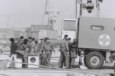 Vojaki v pristanišču stojijo pri tovornjaku, ki ima odprta zadnja vrata. Nekateri vojaki gledajo v njega. Na tleh je pralni stroj in dva večja paketa.
