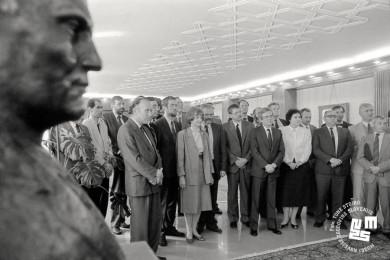 Člani vlade stojijo v polkrogu v dvorani.