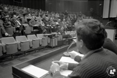 Člani sedijo na tribuni, oseba sedi na govorniškem odru.