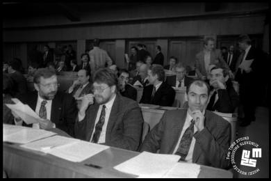 Dimitrij Rupel, Igor Bavčar se pogovarjata. Poleg sedi Janez Janša in se smehlja. V ozadju člani skupščine.