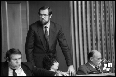 Lojze Peterle stoji  med pogovorom s člani parlamenta.