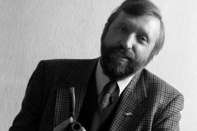 Dimitrij Rupel se smehlja, v roki drži pipo.