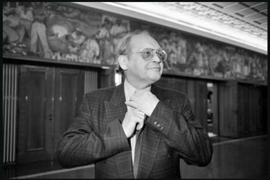 Stane Stanič si na hodniku državnega zbora popravlja kravato.
