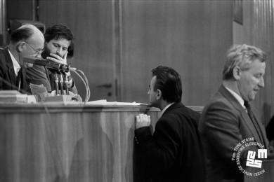 Član skupščine je pristopil k Francetu Bučarju, ki sedi na govorniškem odru. Poleg Bučarja sedi drugi član skupščine. Razpravljajo.