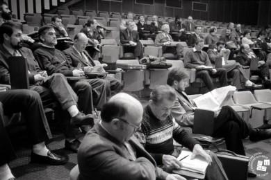 Člani sedijo na tribuni v dvorani.