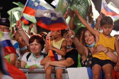 Množica ljudi maha z zastavami ob sprejemu športnikov.