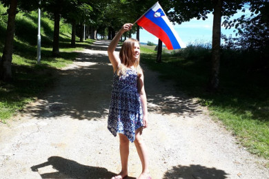 A little girl holds the flag on a stick.